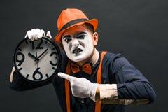 pantomima asustadiza del payaso con un reloj en sus manos, en un backg oscuro fotos de archivo