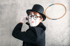 Pantomime actor performing with badminton racket. Comedy mime artist in suit, gloves, glasses, make-up mask and hat Royalty Free Stock Photos