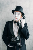 Pantomime actor performing with retro telephone Stock Photo