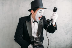Pantomime actor performing with retro telephone Stock Image