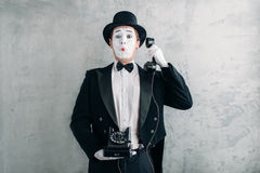 Pantomime actor performing with retro telephone. Pantomime theater actor with makeup mask performing with retro telephone. Comedy artist in suit, gloves and hat stock photography