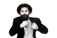 Pantomime als Geschäftsmann, der Geld in seine Tasche einsetzt stockfotos