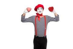 pantomime de sourire tenant les boîte-cadeau en forme de coeur photo stock