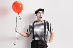 Pantomime, der einen roten Ballon hält und an der Wand sich lehnt stockfotografie