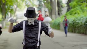 Pantomime drôle plaisantant avec le chat sur la rue banque de vidéos