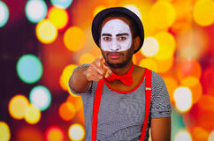 Pantomime man wearing facial paint pointing into camera, standing with arms crossed, blurry lights background Stock Photography