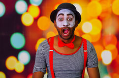 Pantomime man wearing facial paint posing for camera interacting making funny expressions, blurry lights background.  Stock Photo