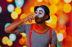 Pantomime man wearing facial paint posing for camera, using hands interacting body language, blurry lights background.  Royalty Free Stock Images