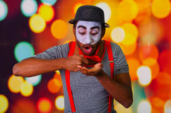 Pantomime man wearing facial paint posing for camera, using hands interacting body language, blurry lights background.  Stock Photo