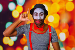 Pantomime man wearing facial paint posing for camera, using hands interacting body language, blurry lights background Stock Image