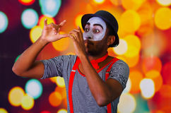 Pantomime man wearing facial paint posing for camera, using hands interacting body language, blurry lights background.  Stock Image