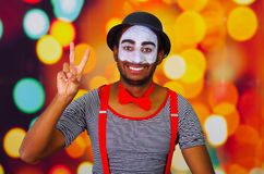 Pantomime man wearing facial paint posing for camera, using hands interacting body language, blurry lights background Royalty Free Stock Photo
