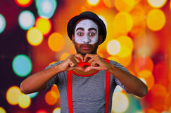 Pantomime man wearing facial paint posing for camera, using hands interacting body language, blurry lights background.  Stock Photos
