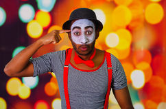 Pantomime man wearing facial paint posing for camera, using hands interacting body language, blurry lights background Royalty Free Stock Image