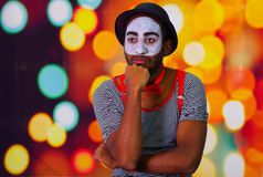 Pantomime man wearing facial paint posing for camera, using hands interacting body language, blurry lights background.  Royalty Free Stock Photos