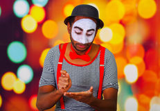 Pantomime man wearing facial paint posing for camera, using hands interacting body language, blurry lights background.  Stock Photography