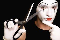 Pantomime mit Scheren auf schwarzem Hintergrund Stockbilder