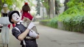 Pantomime plaisantant avec le chat sur la rue banque de vidéos