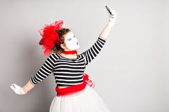 Pantomime prenant une photo de selfie Femme avec le smartphone Concept d'April Fools Day Photographie stock