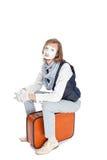 Pantomimeschauspieler, der auf Koffer sitzt Stockbild