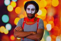 Pantomimman som bär ansikts- målarfärg som poserar för kamera som står med korsade armar, oskarp ljusbakgrund Royaltyfri Bild