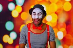 Pantomimman som bär ansikts- målarfärg som poserar för kameran som påverkar varandra göra roliga uttryck, oskarp ljusbakgrund Arkivfoto