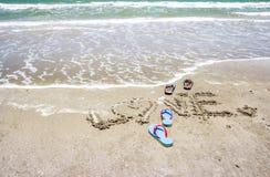 Pantoufles avec amour manuscrit sur la plage Images libres de droits
