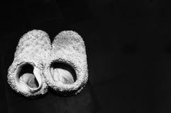 Pantoufles blanches sur un fond noir image stock