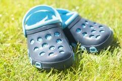 Pantoufles bleues du ` s d'enfants sur l'herbe verte dans le jardin, chaussures pour les enfants, mode de plage pour des enfants, Photo stock