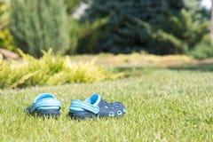 Pantoufles bleues du ` s d'enfants sur l'herbe verte dans le jardin, chaussures pour les enfants, mode de plage pour des enfants, Photographie stock libre de droits