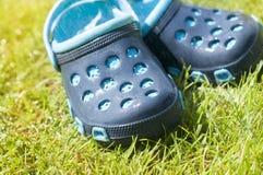 Pantoufles bleues du ` s d'enfants sur l'herbe verte dans le jardin, chaussures pour les enfants, mode de plage pour des enfants, Photographie stock