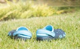 Pantoufles bleues du ` s d'enfants sur l'herbe verte dans le jardin, chaussures pour les enfants, mode de plage pour des enfants, Photo libre de droits