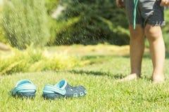 Pantoufles bleues du ` s de jambes et d'enfants de bébé sur l'herbe verte dans le jardin, chaussures pour des enfants, le concept Photo libre de droits