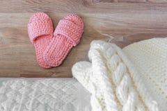 Pantoufles de couvre-lit blanc tricoté et de femmes roses près du lit photographie stock