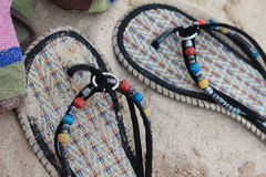 Pantoufles de femme sur le sable Images libres de droits