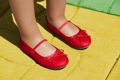 Pantoufles de Rubis sur la route jaune Image stock