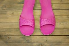Pantoufles femelles sur le plancher ou le fond en bois photographie stock libre de droits