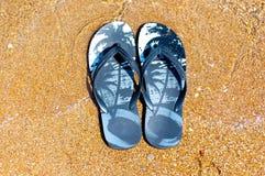 Pantoufles sur la plage Photos libres de droits