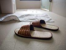 Pantoufles sur le plancher dans la salle de bains Photo stock