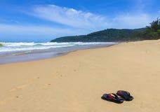 Pantoufles sur le rivage de la mer chaude Photos stock