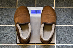 Pantoufles vides sur une échelle de poids Images stock