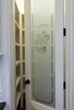 Pantry door. Detail of pantry door with empty shelves behind stock image