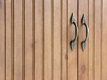 Pantry Doors. With brass handles. Simulated odessa pine finish. Natural lighting Stock Photo