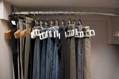 Pants hanging organized in closet. Pairs of jeans and pants hang on hangers in a row in the closet, well organized royalty free stock images