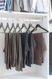 Pants hanging on rack in wardrobe Stock Image