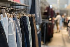 Pants and jeans on the racks in clothing store. Row of pants and jeans on the racks in clothing store, shopping. Blur background with clothes shop interior Stock Photography