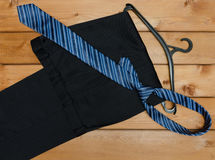 Pants, tie and hanger. On wooden table background Royalty Free Stock Images