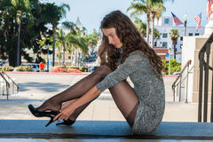 Pantyhose at street level. Pretty backlit brunette in black pantyhose, short dress, and pumps seated over Downtown adjusting her shoe royalty free stock photography