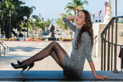 Pantyhose at street level. Pretty backlit brunette in black pantyhose, short dress, and pumps seated over Downtown leaning back royalty free stock photo