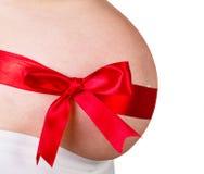Panza de la mujer embarazada con el arco Foto de archivo